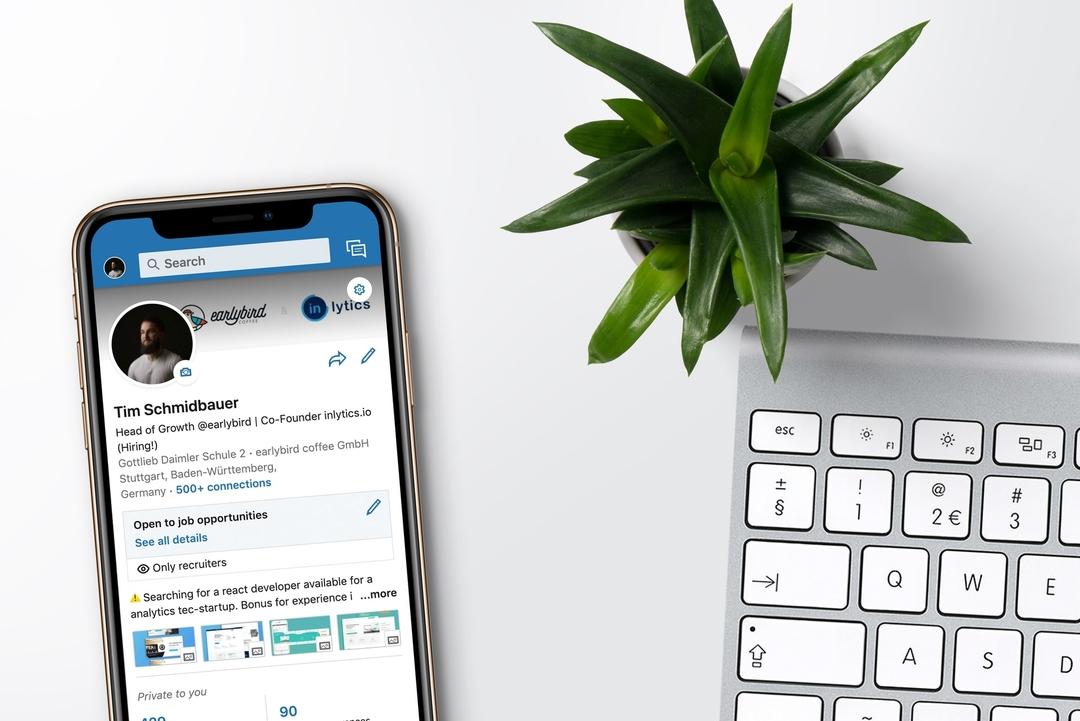 Gauche: téléphone avec un profil LinkedIn. Droite: clavier d'ordinateur et plante verte.